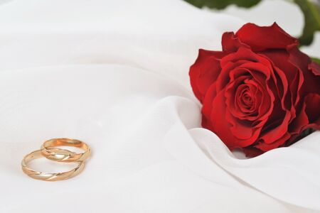 Wedding concept with rose and rings on  white silk photo