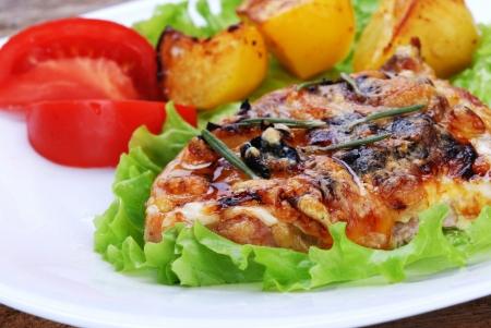gebratenes Fleisch, gebackene Kartoffeln und Tomatenscheiben