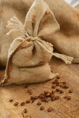 hessian bag: Coffee beans around a hessian bag on wooden board Stock Photo