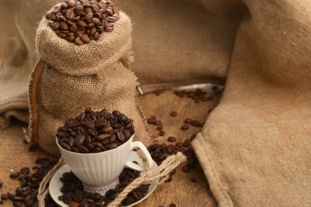 Roasted coffee beans in jute sack and cup on wooden background Stock Photo - 16277911