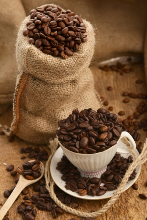 Roasted coffee beans in jute sack and cup on wooden background photo
