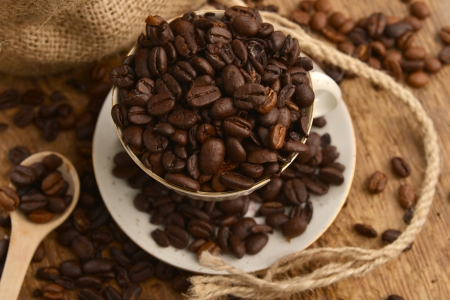 Roasted coffee beans with cup on jute hessian background  Stock Photo - 16278610