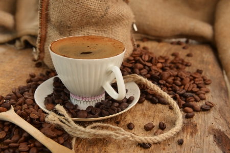 Roasted coffee beans with cup on jute hessian background Stock Photo - 16279373