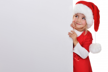 little girl in red santa hat  peeking from  billboard. Stock Photo