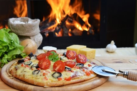 pizza cutter: baked tasty pizza  near wood oven