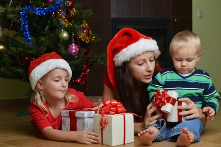 happy children with mother sitting near Christmas tree photo