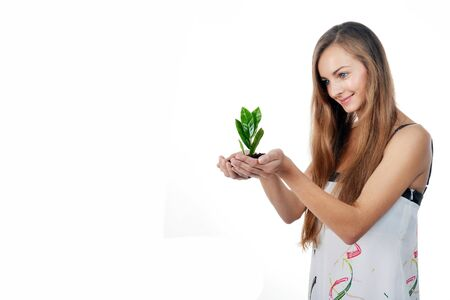 Beautiful young woman with green sprout of tree in her palms Stock Photo - 16774825
