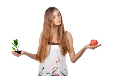 Beautiful young woman holding green sprout of tree and apple Stock Photo - 16775163