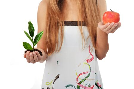 Beautiful young woman holding green sprout of tree and apple Stock Photo - 16528588