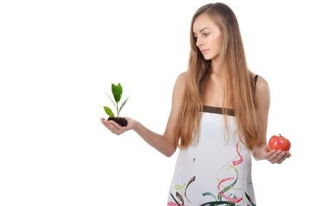 Beautiful young woman holding green sprout of tree and apple Stock Photo - 16775207