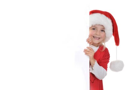little girl in red santa hat  peeking from  billboard. photo