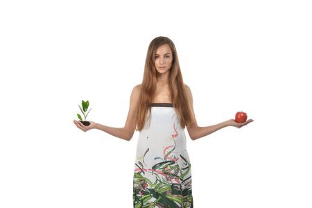 Beautiful young woman holding green sprout of tree and apple Stock Photo - 16776804