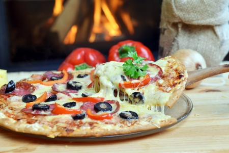 Pizza lifting slice with pepperoni and olives Stock Photo - 16845862