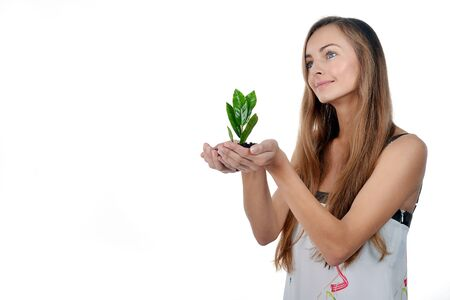 Beautiful young woman with green sprout of tree in her palms photo