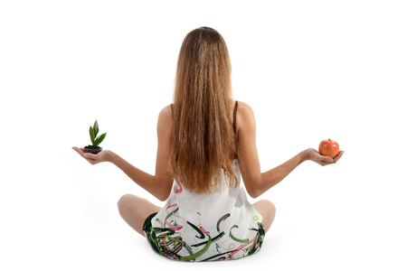 Beautiful young woman with green sprout and apple sitting on floor photo