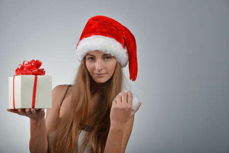Beautiful young woman in santa claus hat holding gift box photo