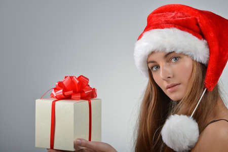 Beautiful young woman in santa claus hat holding gift box Stock Photo - 19797284