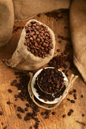 Roasted coffee beans in jute sack and cup on wooden background Stock Photo - 17561499