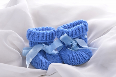 Handmade  baby booties isolated on a white silk background photo