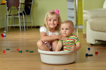 little boy  with his sister sitting  in  tub photo