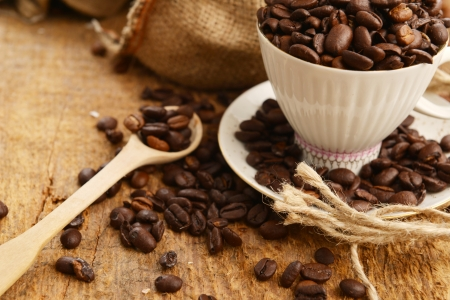 Roasted coffee beans with cup on jute hessian background  photo