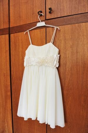 white wedding dress hangs on hanger in room photo