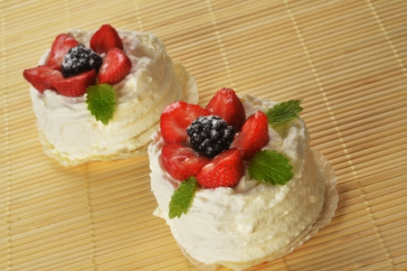 tasty cakes  with white icing and strawberries on bamboo table cloth photo