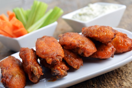 chicken fingers: chicken wings with celery and carrot on wooden background