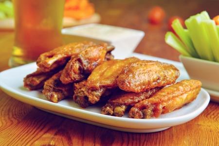 pollo frito: alitas de pollo con apio, zanahoria y un vaso de cerveza Foto de archivo