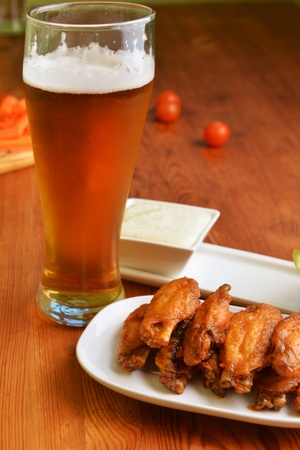 chicken wings with celery, carrot and glass of beer photo