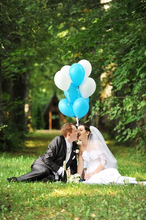 newly-married couple with balloons on green grass in field photo