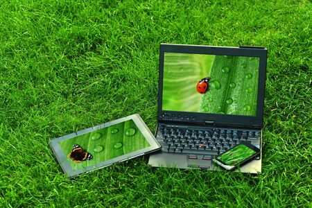 Modern digital tablet PC with mobile smartphone and  laptop on green grass photo