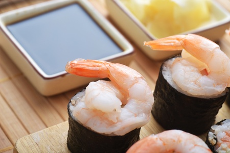 tasty fresh sushi rolls on wooden plate photo