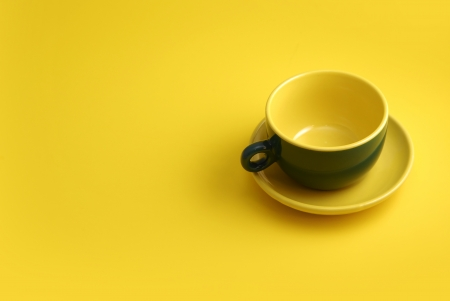 homeware: green cooffee cup on yellow background