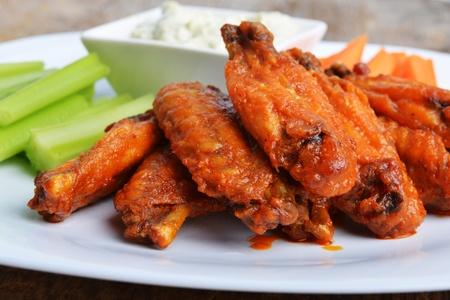 alitas de pollo: alitas de pollo con apio y zanahoria en el fondo de madera