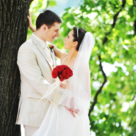 groom and bride in white dress on background of green trees photo