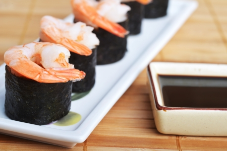 dish with fresh sushi rolls and bowl of sauce on bamboo napkin background  photo