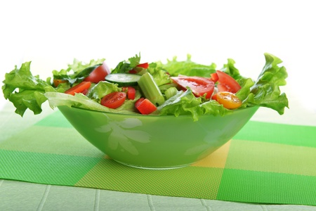 white dish of salad with fresh vegetable on green napkin photo