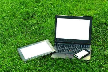 Modern digital tablet PC with mobile smartphone and  laptop on green grass Stock Photo - 19448015