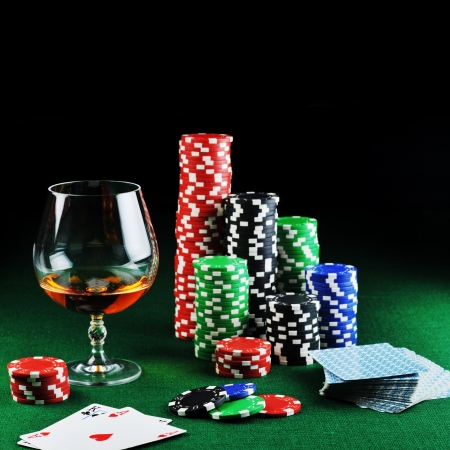 color chips for gamblings, drink and playing cards on green photo