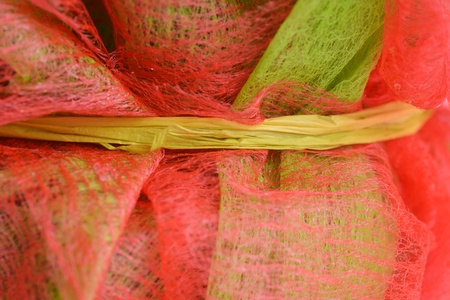 gossamer: Decorative gossamer and red netting fabric used for wrapping flower