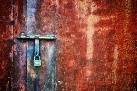 padlock on door of old rusted metal wall photo