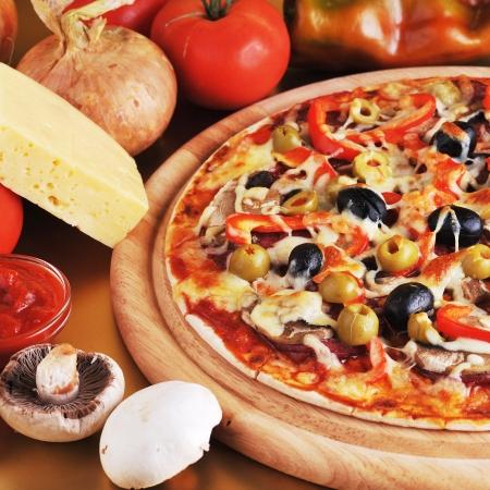 pizza: vers gebakken pizza met pepperoni olijven en paprika Stockfoto