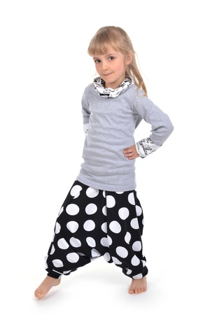 smug: Studio photo of adorable little girl in gray blouson and trousers with polka dots Stock Photo
