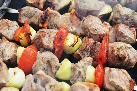 Barbecue with delicious grilled meat  and onions on grill photo