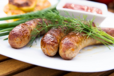 tasty grilled meat sausages on dish photo