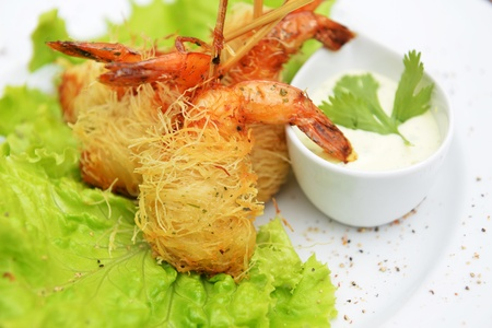 Deep fried shrimp on lettuce leaves with white sauce photo