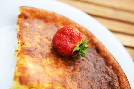 tasty curd casserole with strawberries on plate photo