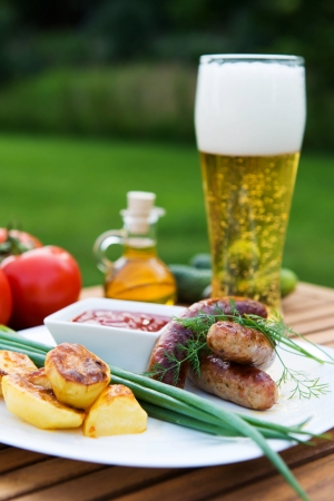 tasty grilled meat sausages  on dish and vegetable photo