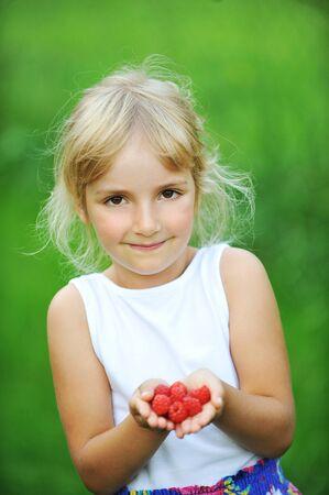raspberry dress: happy smiling little girl holding raspberries